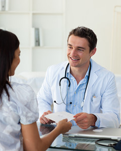 Smiling doctor giving a prescription to his female patient
